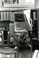 Student reading newspaper in Wollman Library, circa 1970s-80s