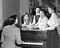 Students gathered around piano, circa 1950s