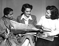 Students read newspaper, October 1950