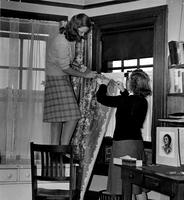 Two students hanging curtains in Hewitt Hall dorm room, 1942