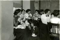 Students in crowded lunchroom, circa 1900s