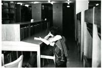 Student reading in Wollman Library stacks, circa 1970s
