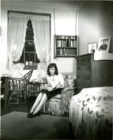 Student sitting on bed in Hewitt dorm room, circa 1945