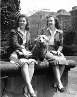 Students sit with dog, circa 1940s