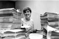 Student with stack of newspapers, circa 1980s