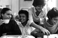 Friends enjoy a meal in cafeteria, circa 1980s