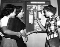 Students read Foreign Student bulletin board, circa 1950s