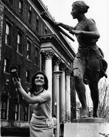 Student carrying torch next to Greek Games statue, circa 1960s-1970s